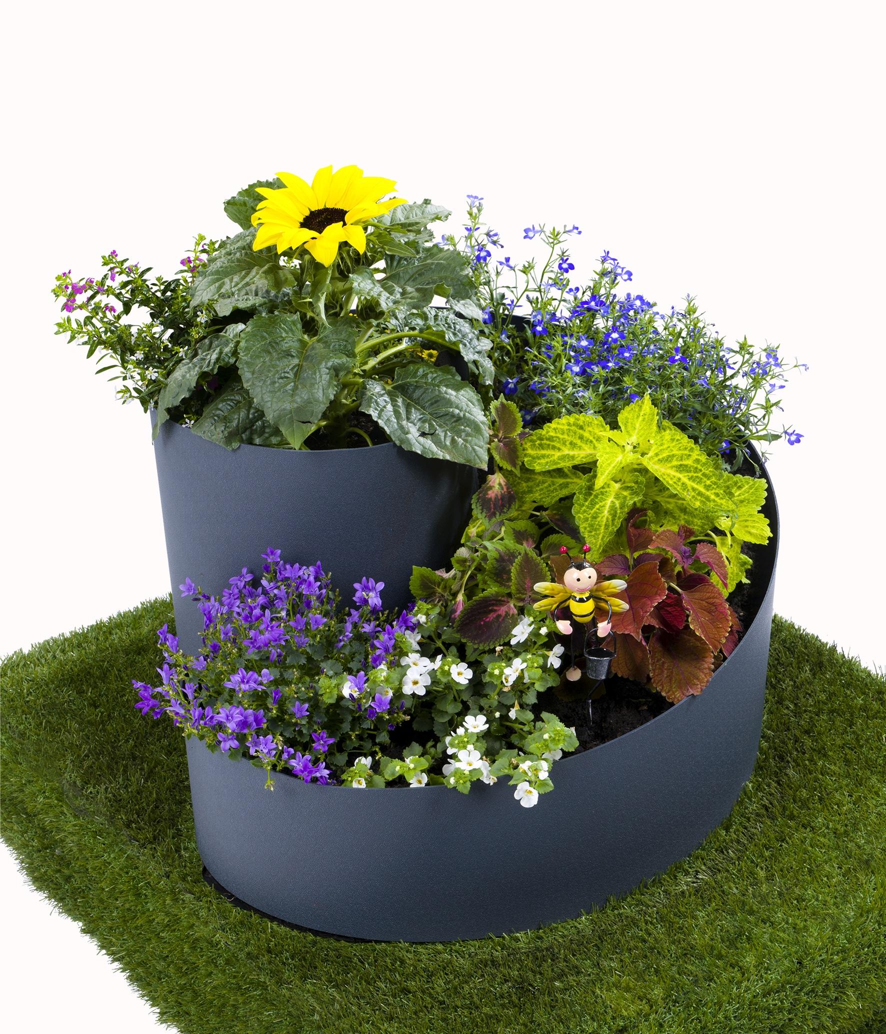 Bepflanzte Kräuterspirale mit bunten Blumen