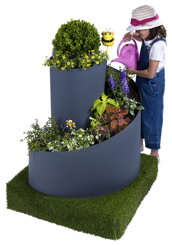 Kind gießt Pflanzen in der FVG Kräuter- und Blumenspirale