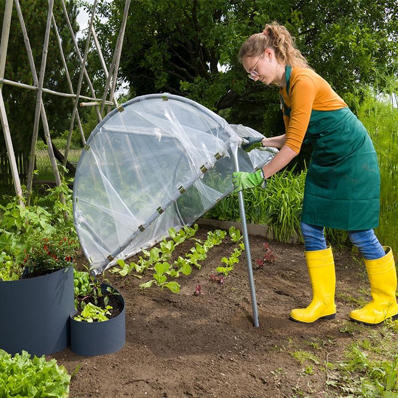Frau im Garten stellt das Frühbeet 2 in 1 auf